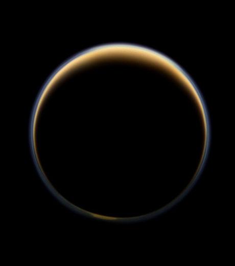 Le côté 'sombre' de Titan auréolé par la lumière du soleil qui forme un anneau coloré autour de la lune (Crédits : NASA/JPL-Caltech/SSI )