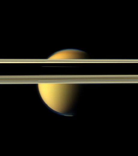 Le visage coloré de Titan obstrué par les obscurs anneaux de la planète Saturne (Crédits : NASA/JPL-Caltech/SSI )