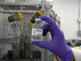 Lauren White, exobiologiste de la Nasa, montre un échantillon de fluide sortant du réacteur chimique simulant la cheminée d'une source hydrothermale. © Nasa, JPL-Caltech