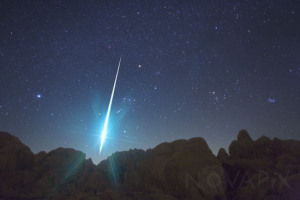 cette photo représente: Un bolide, une étoile filante très brillante, traverse le ciel au-dessus du désert de Mojave en Californie. Photographié le 14 décembre 2009 pendant la pluie des Géminides. Taken at 3:29am Monday Dec 14 2009 during the Gemini Meteor Shower, this is one of the largest fireballs recorded. The dramatic view from Hercules Finger rock formation in Mojave Desert of southwest USA includes the setting prominent winter stars from the dazzling Sirius (left) to constellations Orion and Taurus, with the famous open star cluster Pleiades at the right end.