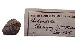 Chassignite (France, 1815). Seule météorite martienne tombée en France jusqu'à ce jour, Chassigny est recouverte partiellement par une croûte de fusion d'un millimètre d'épaisseur. L'étiquette indique qu'il s'agit d'une achondrite, c'est à dire une météorite sans chondres. Les chassignites sont des cumulats d'olivine, c'est à dire des roches constituées presque exclusivement de ce minéral. Chassigny, qui constituait un type à part de météorites martiennes (le C de SNC), est restée longtemps unique, jusqu'à la découverte de NWA 2737 (nommée Diderot) au Maroc en août 2000. (Crédit photo : Martin Horejsi).