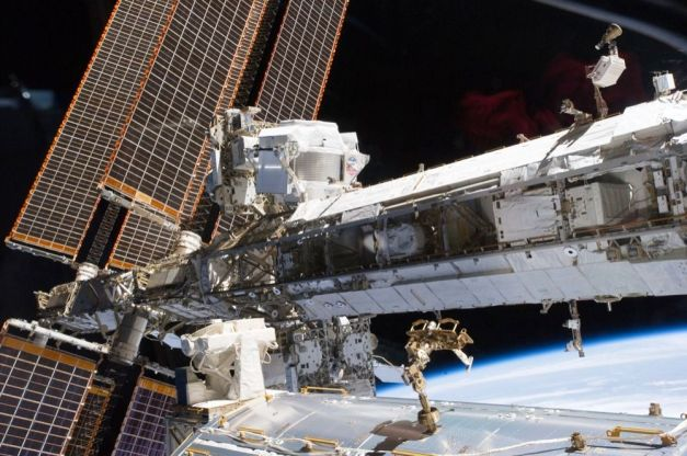 AMS-02 (devant les panneaux solaires, en haut) est installé sur la Station spatiale internationale (ISS). Il chasse la matière noire depuis presque quatre ans et devrait encore le faire pendant plusieurs années. © Nasa