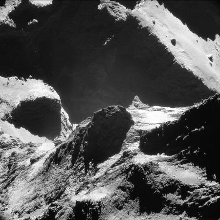 Paysages variés à la surface de la comète 67P/Churyumov-Gerasimenko, photographiée ici par Rosetta le 19 octobre 2014 à seulement 9,9 km du centre du noyau. Les reliefs au premier plan appartiennent au petit lobe où s'est posé Philae le 12 novembre. Une partie du plus grand lobe est visible à l'arrière-plan. Entre les deux, dans l'ombre, au pied des parois sombres, il y a le « cou » de la comète, un des sites les plus actifs. La résolution de l'image est de 77 cm par pixel. © Esa, Rosetta, NavCam – CC BY-SA IGO 3.0