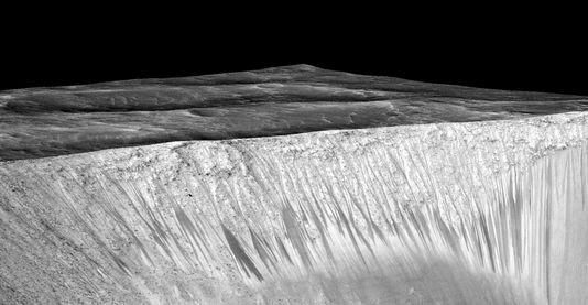 Traînées sombres sur les pentes du cratère martien Garni. ces trainées mesurent quelques centaines de mètres.