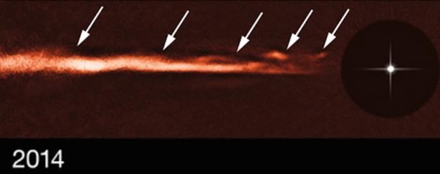 Sur cette image, prise en 2014 à l'aide de l'instrument SPHERE, on voit l'étoile (à droite) et son disque de poussière (de couleur orangée), vu par la tranche. Au milieu de ce disque des sortes d'ondulations (matérialisées par les flèches banches) intriguent les chercheurs. ©Nature